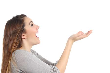 boca abierta: Perfil de una mujer sosteniendo algo en blanco sorprendido aislado en un fondo blanco