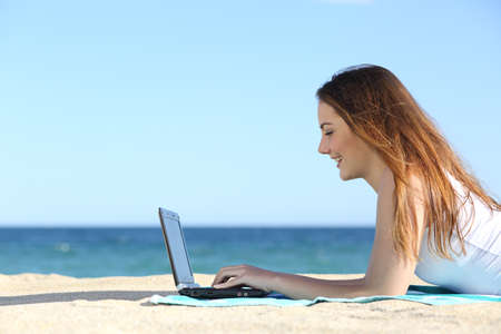 web side: Side view of a teenager girl browsing a laptop on the beach with the sea in the background             Stock Photo
