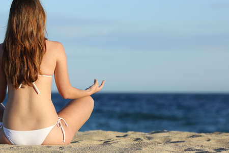 Woman meditating yoga on the beach in summer with the horizon over the sea in the background photo