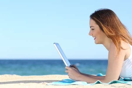 Teenager girl browsing social media in a tablet on the beach with the sea in the background              photo