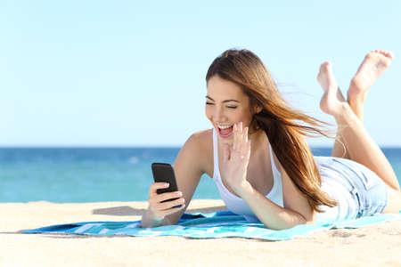 taking video: Teenager girl waving during a smart phone video call in vacations with the sea in the background Stock Photo