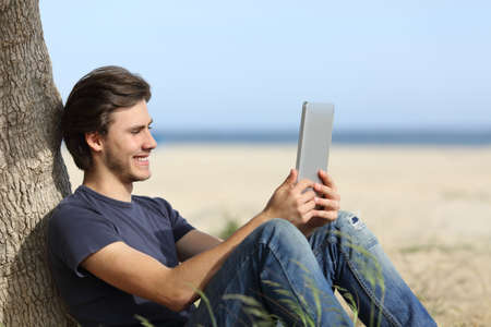 Happy man reading a tablet reader sitting on the beach with the horizon in the background photo