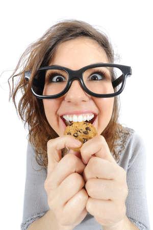白い背景で隔離のクッキーを食べる面白いオタクの女の子