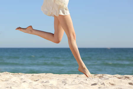 Beautiful woman long legs jumping on the beach with the sea in the background                  Stock Photo