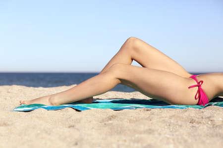 depilacion con cera: Mujer de la belleza perfecta depilación piernas para tomar el sol en la arena de la playa con horizonte en el fondo Foto de archivo
