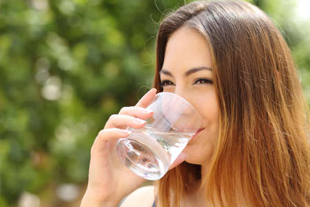 Gelukkige gezonde vrouw drinken van vers water uit een glas buiten met een groene achtergrond
