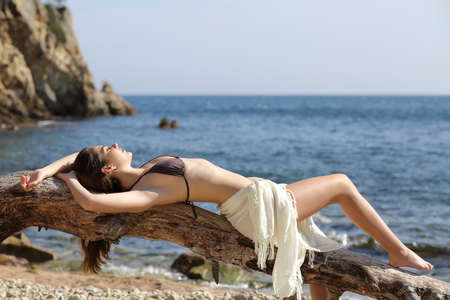 pareo: Sunbather beautiful woman sunbathing on the beach with the sea in the background