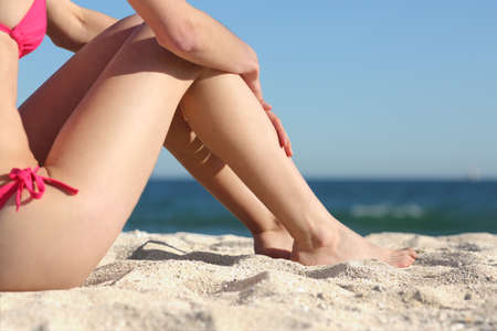 Sunbather woman legs sitting on the sand of the beach resting with the sea in the background               photo