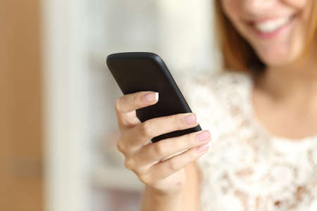 Close up of a woman hand using a smart phone at home with her smile in the background         Stock Photo
