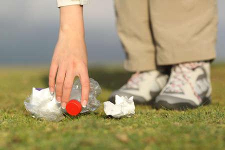 Eco wandelaar de hand verzamelen van afval in het gras van de berg