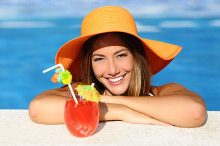 perfect teeth: Beauty woman with perfect smile enjoying a cocktail in a swimming pool on vacations with blue water in the background                  Stock Photo