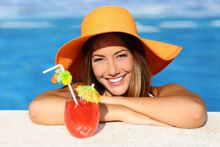 ortodoncia: Belleza de la mujer con sonrisa perfecta disfrutando de un cóctel en la piscina en vacaciones con agua azul en el fondo