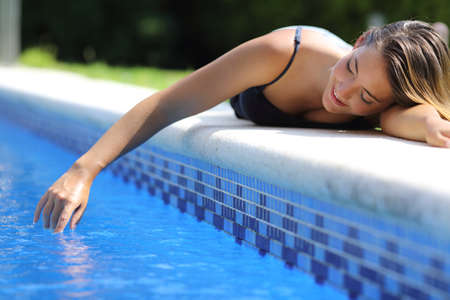 Casual happy woman in vacations playing with water in a swimming pool from poolside            Stock Photo