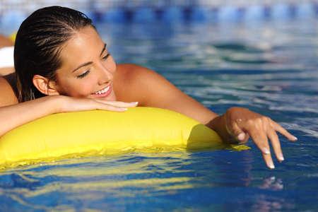 sonnenbaden: Frau Baden und Spielen auf einer Matratze mit Wasser auf ein Schwimmbad in Urlaub