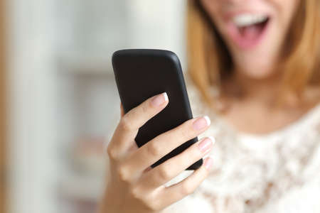 Close up of a surprised woman hand holding and using a smart phone at home             photo