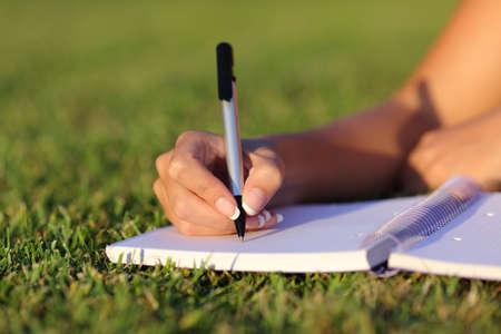 Primo piano di una scrittura mano della donna su un notebook all'aperto sdraiato sul prato in un parco
