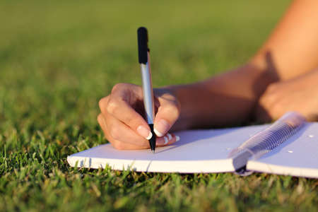 Close up of a woman hand writing on a notebook outdoor lying on the grass in a park