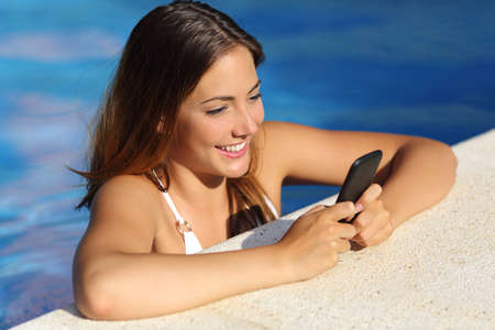 Happy girl using a smart phone white bathing in a swimming pool in summer vacations with blue water  photo