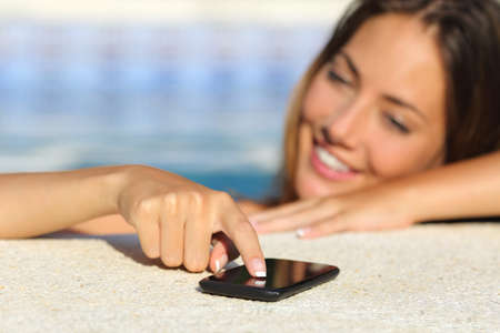 Close up of a happy woman in vacations texting in a smart phone bathing in a swimming pool with water  photo