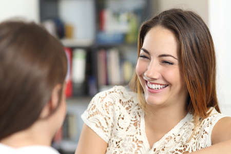 Happy woman taking a conversation and laughing with a friend at home