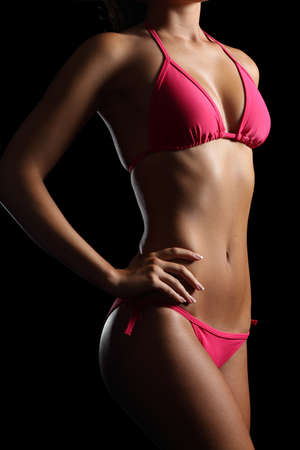 Perfect fitness body wearing a pink bikini isolated on a black  photo
