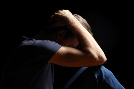 Depressed teenager man with hands over head isolated in a black background