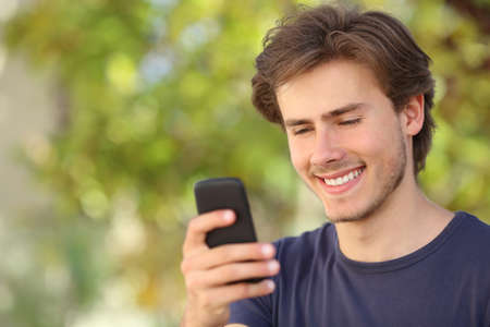 Happy man using a smart phone outdoor with a green background photo