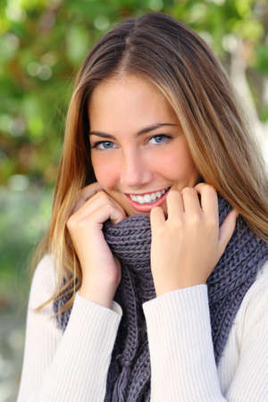Mujer hermosa con una sonrisa perfecta blanca y ojos azules en invierno vestido calurosamente