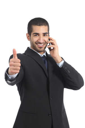 Arab businessman on the mobile phone with thumb up isolated on a white background                 photo