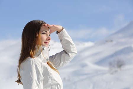 Hiker woman looking forward in the snowy mountain with her hand on forehead photo