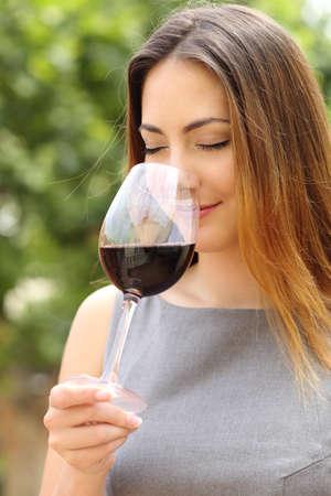 Somelier mujer que huele y degustación de vino tinto con un fondo verde