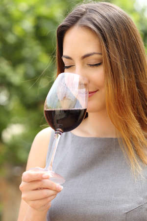 Somelier woman smelling and tasting red wine with a green background