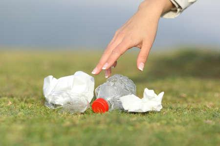 Vrouw de hand verzamelen van afval van het gras in de bergen met een kopie ruimte Stockfoto