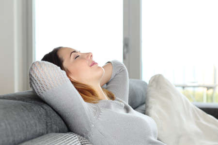 head home: Happy relaxed woman resting on a couch at home with arms in the head