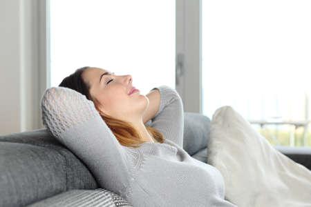 descansando: Mujer relajada feliz descansando en un sofá en casa con los brazos en la cabeza