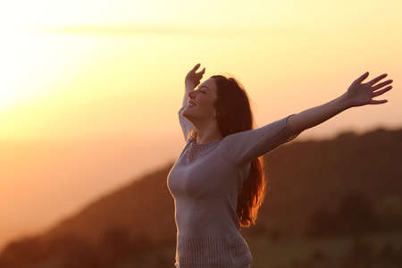 feelings of happiness: Backlit of  a woman at sunset breathing fresh air raising arms