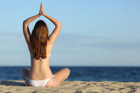 Woman practicing yoga exercises on the beach in summer with the horizon over the sea in the background photo