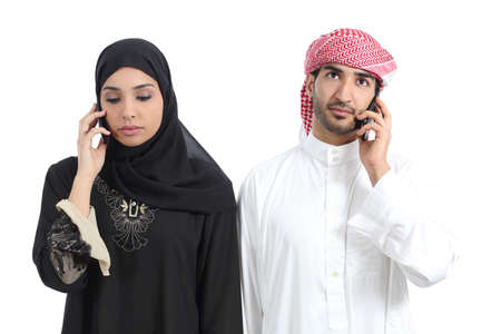 Arab couple disgusted on the phone isolated on a white background         photo