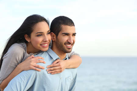 Pareja árabe coqueteando a cuestas en el amor en la playa con el mar de fondo