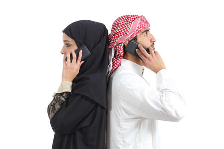Distant arab couple calling on the phone isolated on a white background            Stock Photo