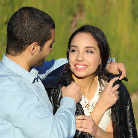Happy arab couple flirting while gentleman cover her with his jacket in a park with a green background