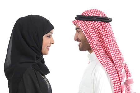 Side view of an arab saudi couple looking each other isolated on a white background             photo