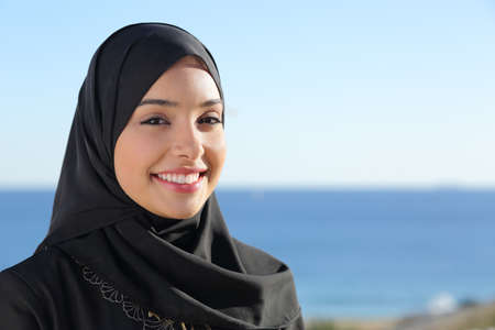 Beautiful arab saudi woman face posing on the beach with the sea in the background                 photo