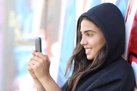 street style: Skater style teen girl reading happy her smart phone with an unfocused graffiti wall in the background Stock Photo