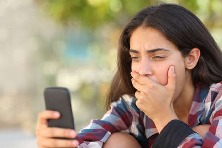 Worried teenager girl looking at her smart phone in a park with an unfocused background