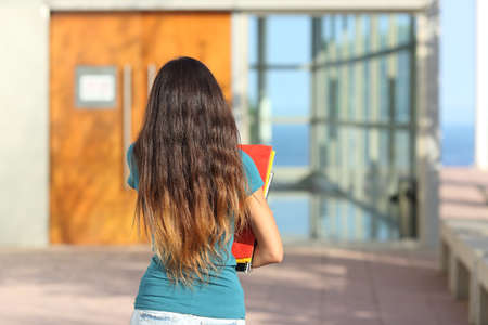 Back view of a teen girl walking towards the school with the door in the background photo