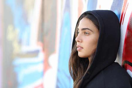 Profiel portret van een skater stijl tiener meisje met een ongericht graffiti muur op de achtergrond Stockfoto