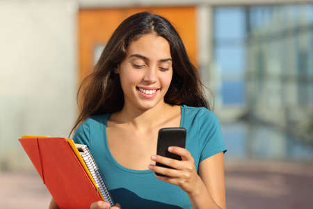 directorio telefonico: Chica adolescente estudiante caminando mientras mira su teléfono inteligente con la puerta de la universidad en el fondo