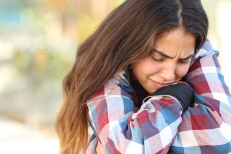 Close up of a teenager girl worried and sad crying outdoors photo