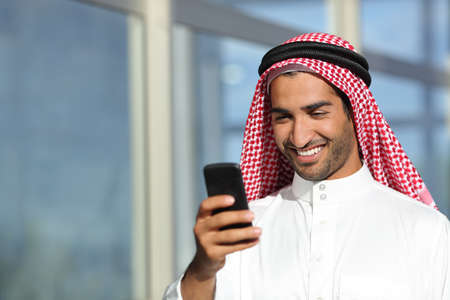 Arab saudi businessman working  with his phone with an office building in the background
